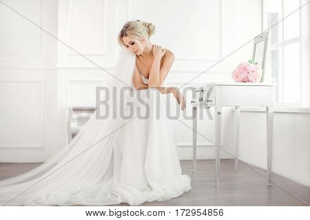 Classical young gourgeous bride. Studio interior fashion shot of fashion model in wedding dress with bouquet of flowers sitting in white room with chair bedside table and mirror. Blonde woman portait with profeshional make-up and hairstyle.