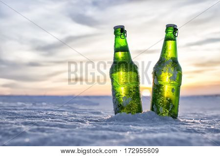 Bottles of cold beer in the snow at sunset