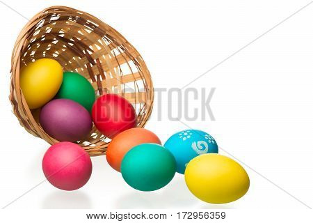 Wicker Basket And Strewn Eggs On A White Background
