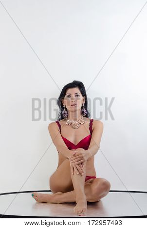 a girl in red linen sits on the floor