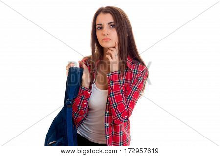 serious stylish student girl with backpack on her shoulders posing isolated on white