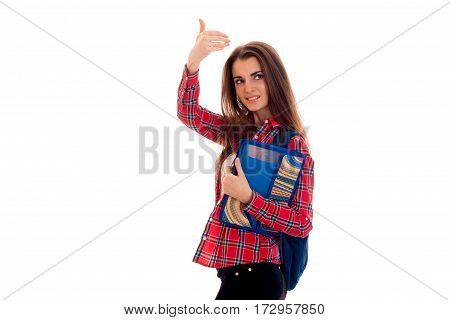 pretty stylish student girl with backpack on her shoulders and folder for notebooks in her hands posing isolated on white