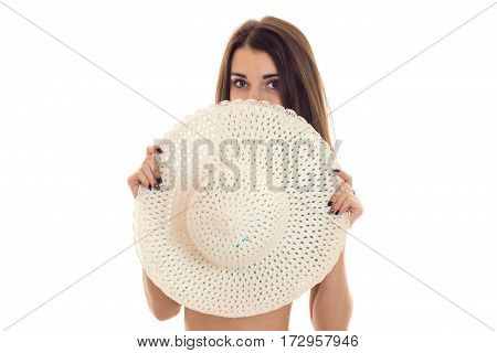 attractive young sexy brunette woman without clothes hide her boobs behind a straw hat with brim and looking at the camera isolated on white
