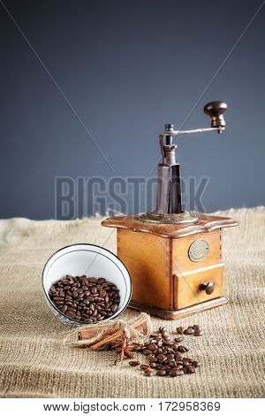 Coffee beans and an old coffee grinder on jute background selective focus.