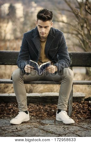 Male student reading book outdoor. Handsome young man reads a book sitting outside on a bench in city park