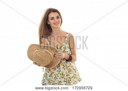 cheerful brunette woman in sarafan with floral patter and straw hat posing and smiling on camera isolated on white