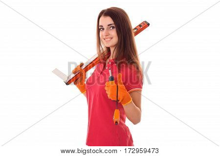 young charming brunette woman in uniform makes renovation with tools in her hands smiling on camera isolated on white