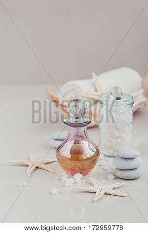 Composition of spa treatment with perfume or aromatic oil bottle surrounded by flowers on bright background. Luxury lifestyle and spa concept.