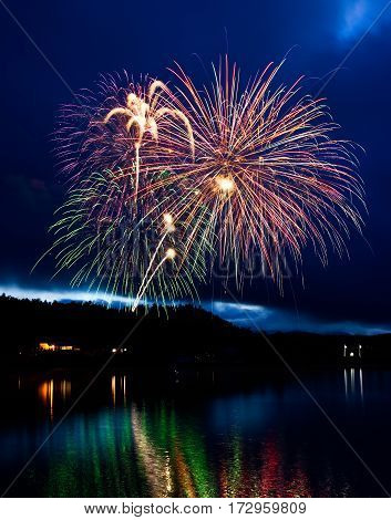 Fireworks reflecting off the water over a lake.