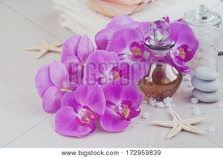 Composition of spa treatment with perfume or aromatic oil bottle surrounded by purple orchids flowers. Luxury lifestyle and spa concept.