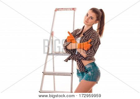 young adorable brunette woman in uniform makes renovation with ladder looking at the camera and smiling isolated on white