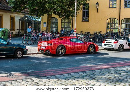 BAMBERG, GERMANY - Circa September, 2016: Bright red Ferrari 458 supercar parked in a cobbled street in Bamberg, Bavaria, Germany, a symbol of wealth, luxury and speed with crowd of tourists behind