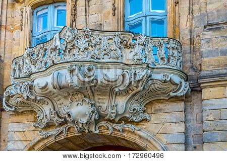BAMBERG, GERMANY - Circa September, 2016: Ornate historic Baroque carved stone balcony on the exterior facade of an old building in Bamberg, listed as a World Heritage Site for medieval architecture