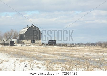 Old stone & wood barn on the edge of a snowy field.