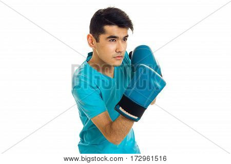 serious young sports man in blue gloves and uniform practicing boxing isolated on white