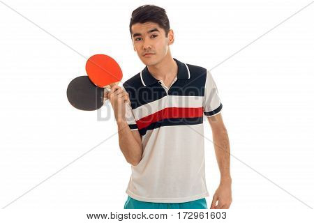 Handsome young sports man with rackets in uniform practicing table tennis isolated on white