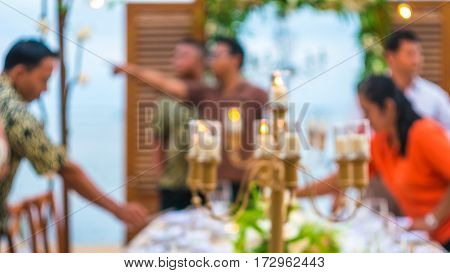 Blurred of Table in the Restaurant witch candles and servants on the Beach, Bali. Swirl Bokeh