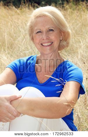 Portrait of a beautiful seventy year old lady with beautiful bright smile. Outside in the garden.