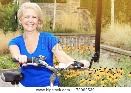 Happy smiling beautiful seventy year old lady on a bicycle.