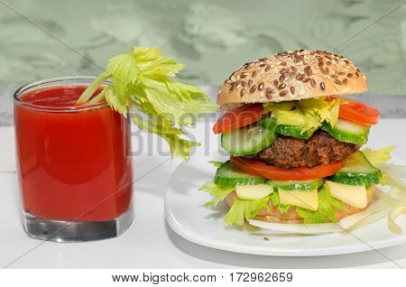 Great Burger and tomato juice with celery in the glass.
