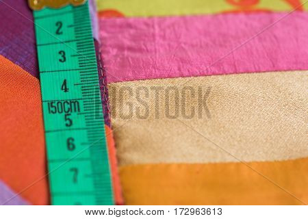 the tailor's centimeter lies on a color scrappy blanket close up.