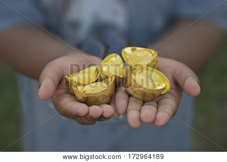 Chinese new year ornament--Stack of gold ingots. Boy holding gold extended. Translation in English meaning lucky and richly