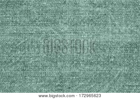 Homespun hemp cloth. Close-up of texture fabric cloth textile background. Homespun hemp fabric material. Homespun hemp canvas. Natural authentic cloth. Gray-green color