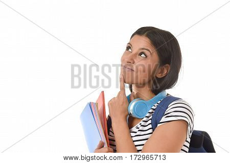 young beautiful and trendy latin student girl holding notepad folder and book carrying backpack smiling happy thinking in future university and college education isolated on white background
