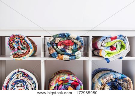 color blankets in style a patchwork put in a roll lie in different cells of a box and the place for the text over them from above.