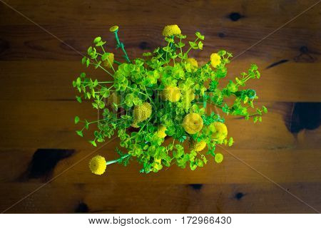 Bouquet of spring beautiful fresh yellow flowers from the top on the wooden table, tanacetum flowering plant
