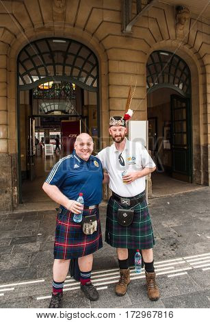 LUXEMBOURG LUXEMBOURG - JUN 5 2016: Penicuik Tartan Army - Scotland national footbal team members smiling posing with a beer in front of Luxembourg central Train station. The Tartan Army is a name given to fans of the Scotland national football team.