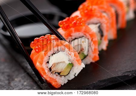 Japanese Cuisine. Salmon Sushi Roll In Chopsticks On A Stone Plate Over Concrete Background.