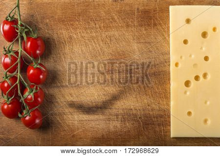 Emmental cheese with bunch of cherry tomatoes on wood background with copy space