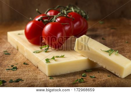 Emmental cheese with cherry tomatoes and herbs on wooden cutting board