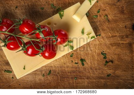 Emmental cheese with cherry tomatoes and parsley on wooden cutting board