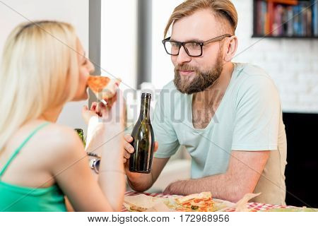 Young couple dressed casually having a lunch with pizza and beer at home