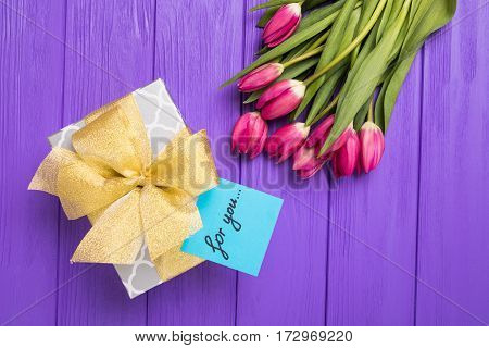 Purple tulip bouquet, blank greeting card and gift boxes.