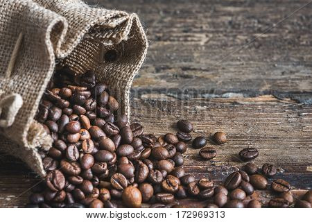 Roasted Coffee Beans Spilled out of Burlap Sack on Wooden Background. Copy Space for Text.