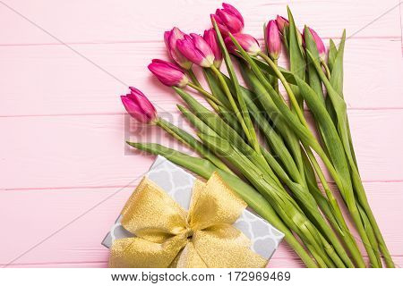 Purple tulip bouquet, blank greeting card for you and gift boxes. Top view over purple wooden table