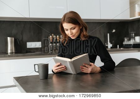 Image of young amazing lady dressed in black sweater sitting at kitchen. Reading book.