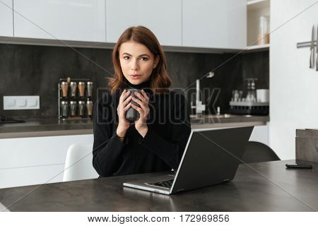 Photo of young attractive woman dressed in black sweater sitting at kitchen holding cup of coffee. Chatting by laptop.