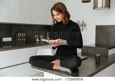 Photo of young smiling woman dressed in black sweater sitting at home indoors. Reading book.