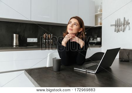 Image of young thoughtful woman dressed in black sweater sitting at kitchen. Chatting by laptop. Looking aside.