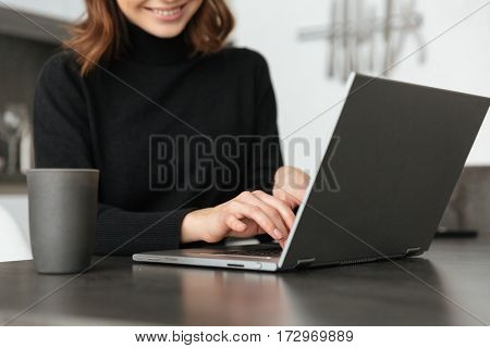Cropped photo of young smiling woman dressed in black sweater sitting at kitchen. Chatting by laptop.