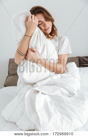Image of young pretty lady dressed in white t-shirt sitting on bed at home indoors.