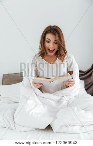 Image of young happy woman dressed in white t-shirt sitting on bed at home indoors while reading book.