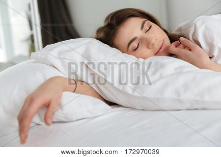 Picture of young tired smiling woman dressed in white t-shirt lies in bed at home indoors and sleeping.