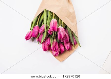 Pink tulips in a package of craft on the wooden background. Pink tulip. Tulips. Flowers. Flower background. Flowers photo concept. Holidays photo concept.