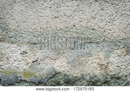 old concrete wall of the house with the remnants of plaster. grunge textured background