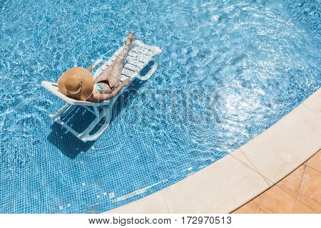 Woman in hat enjoying her summer vacation at the swimming pool
